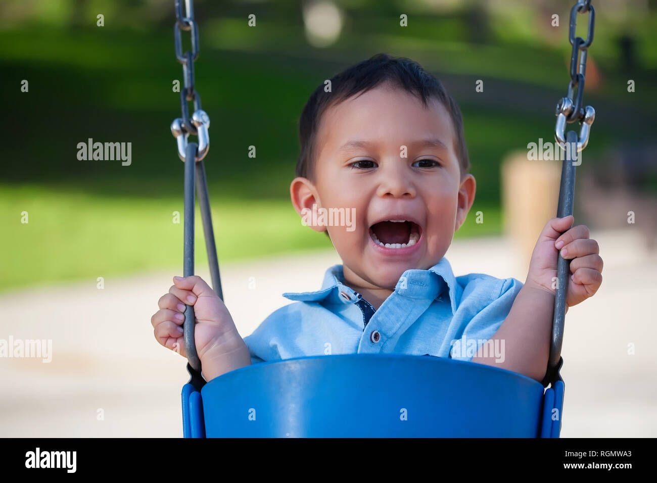 2 year old boy yelling out loud while riding a blue swing at a local park. - Stock Image