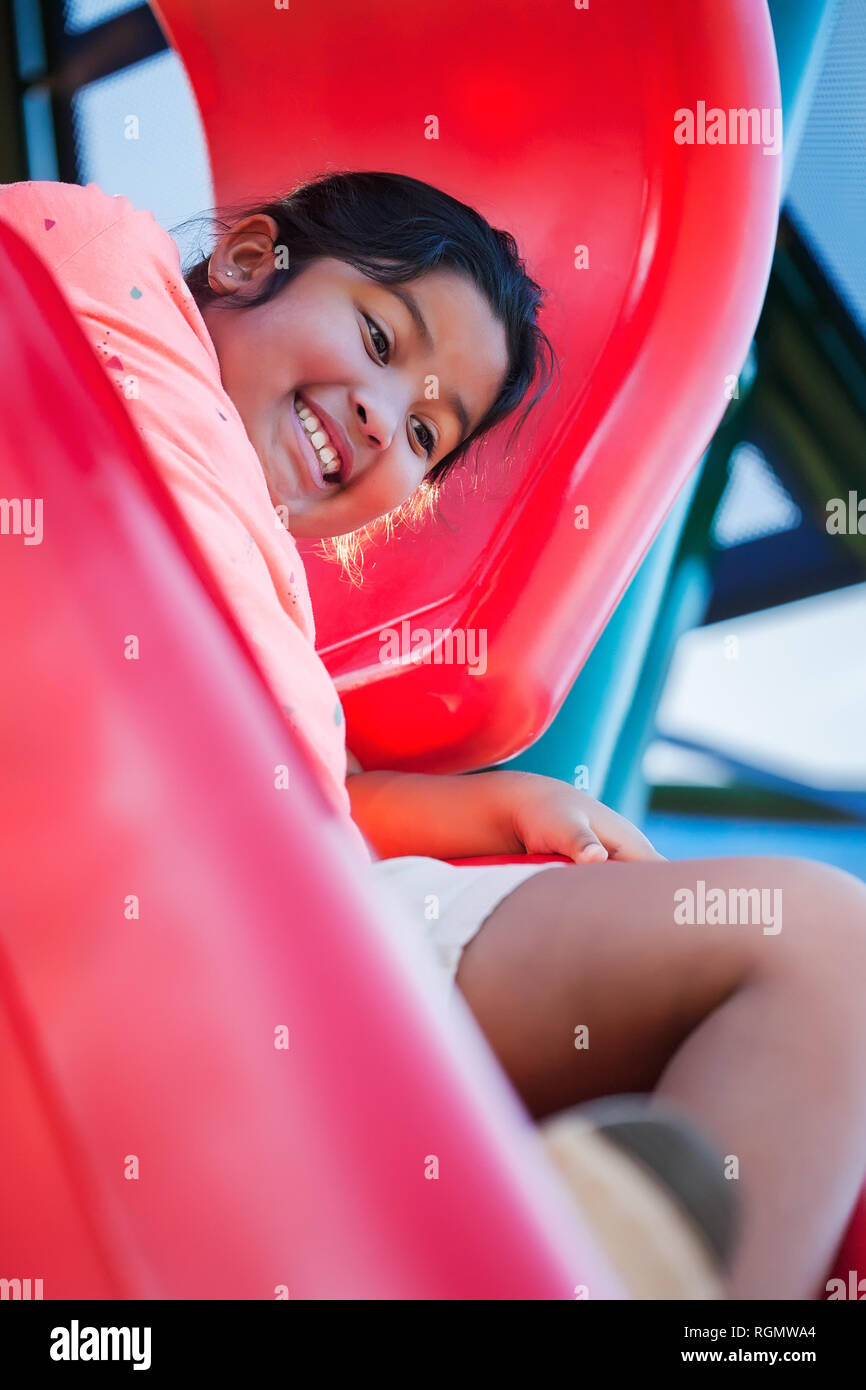 Nervous young girl with and excited facial expression that is holding on to a playground slide before letting go. - Stock Image
