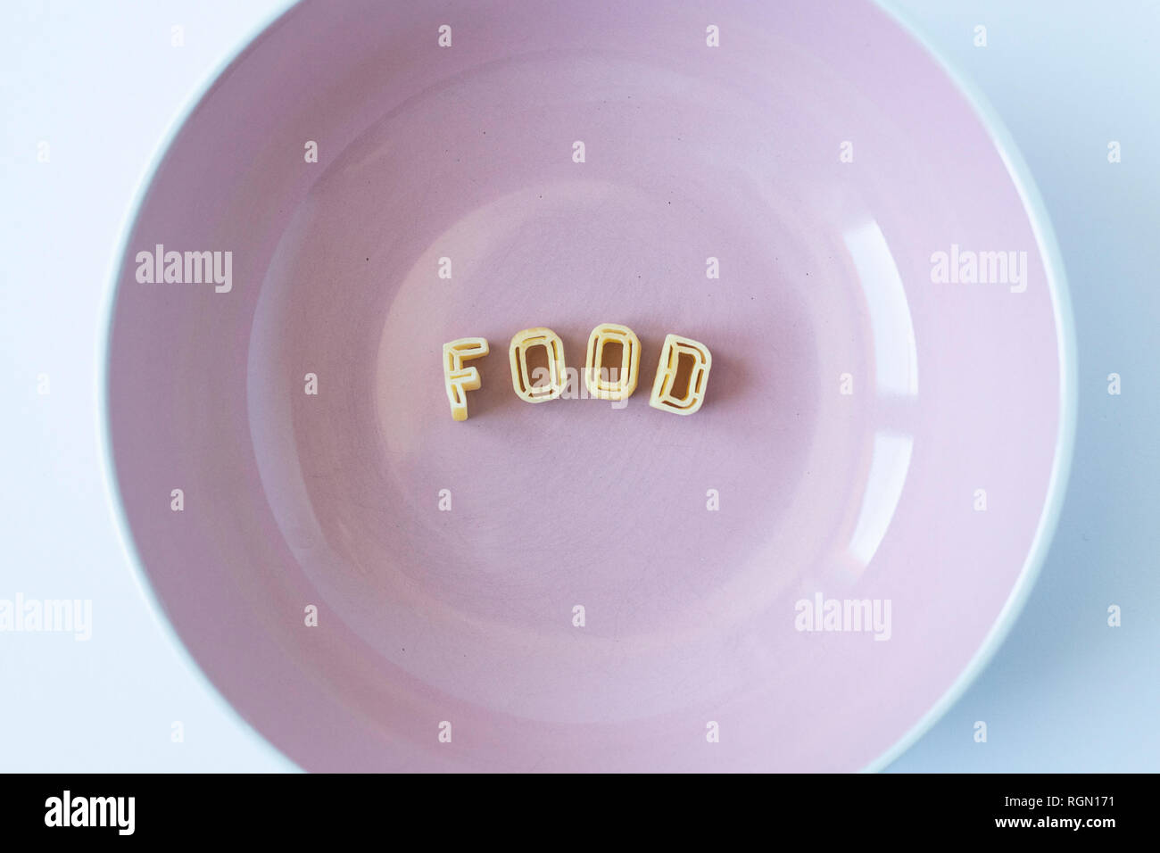 """The word """"food"""" composed with real pasta letters in a pink dish. Stock Photo"""