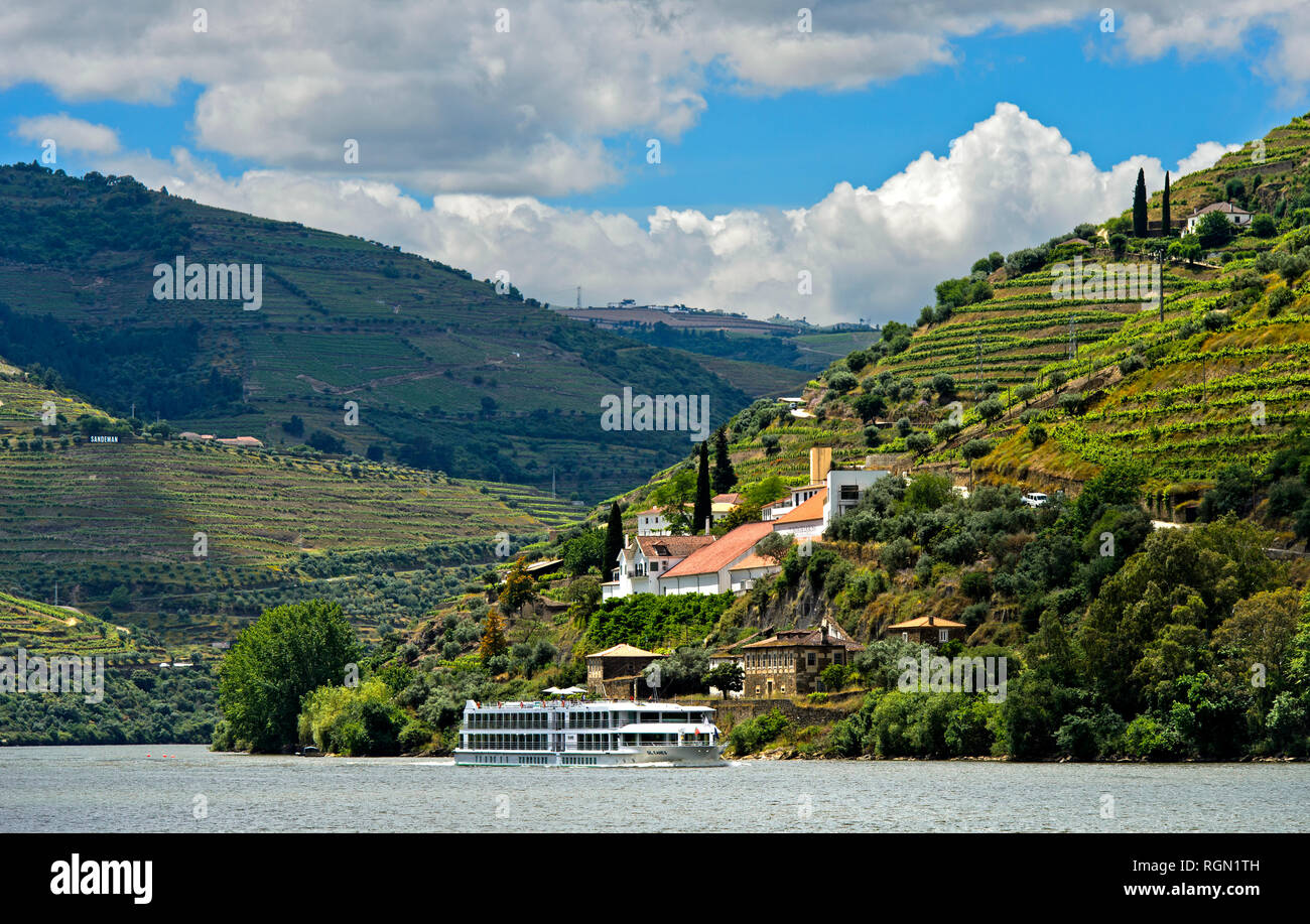 Cruise ship on a river cruise along the Douro River, Quinta de la Rosa on the right side, Pinhao, Douro Valley, Portugal - Stock Image