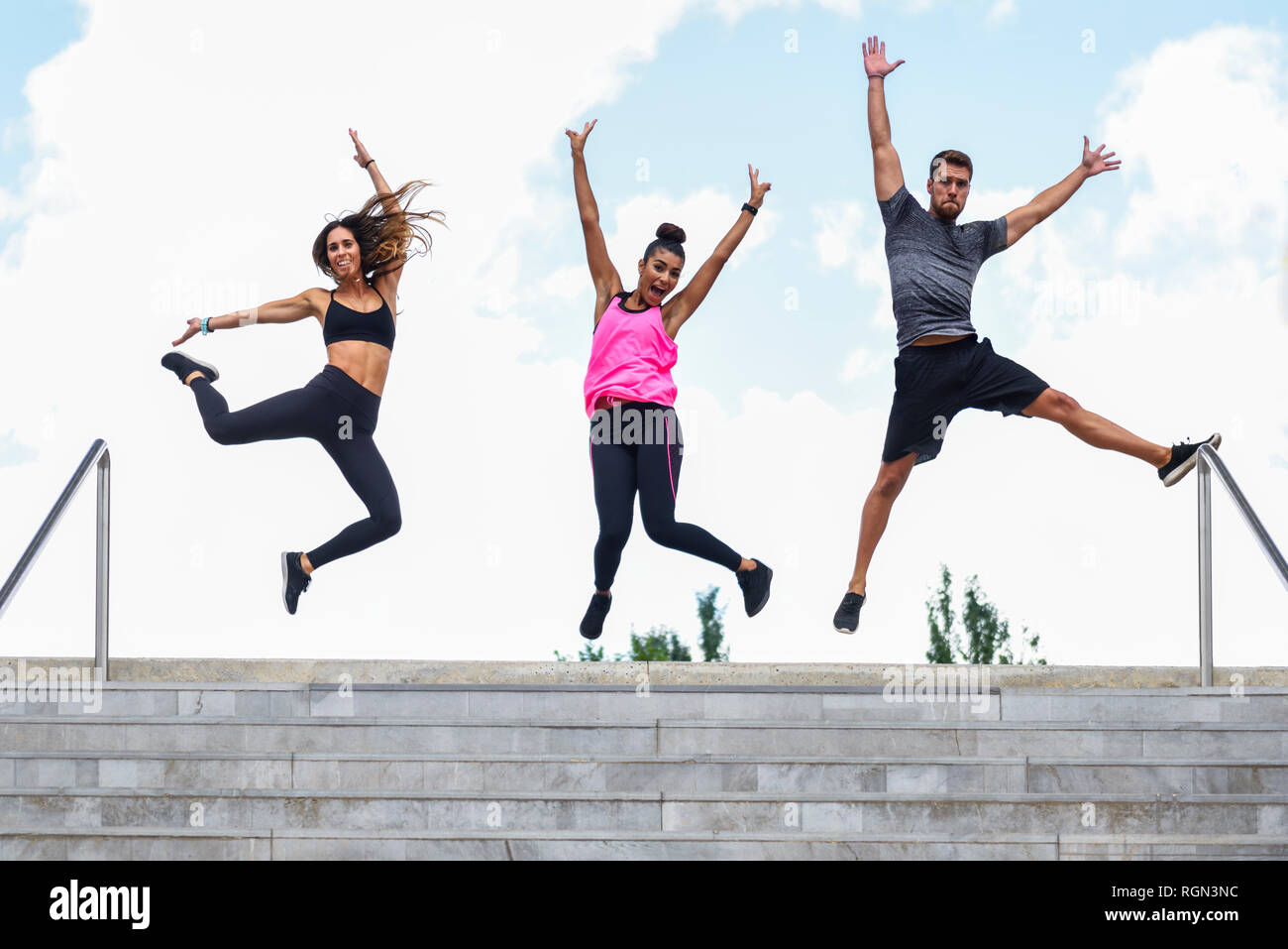 Young athletes jumping for joy on stairs - Stock Image