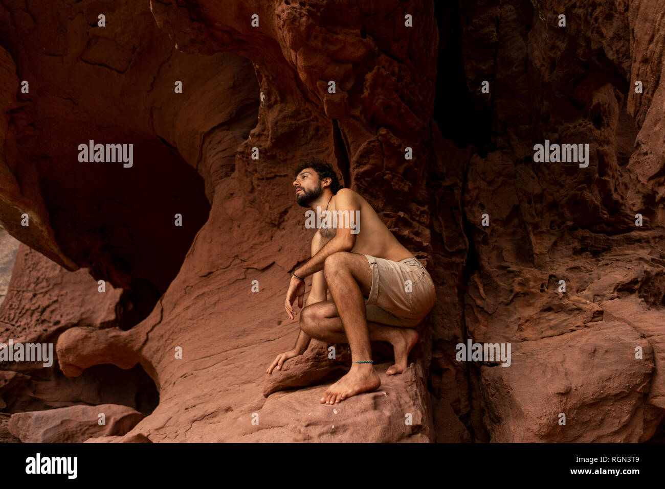 Young man exploring cave - Stock Image