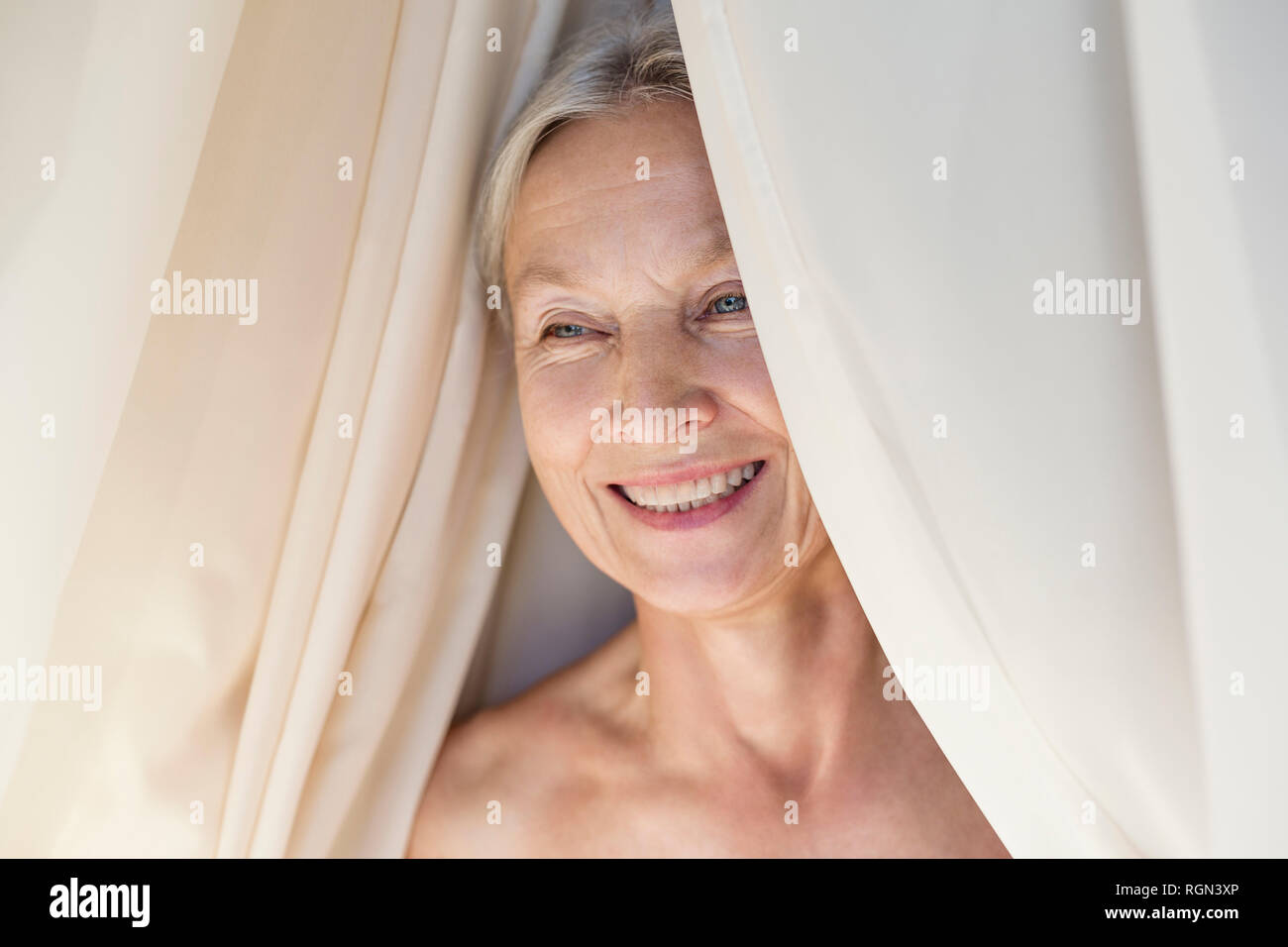 Portrait of relaxed senior woman behind curtain - Stock Image