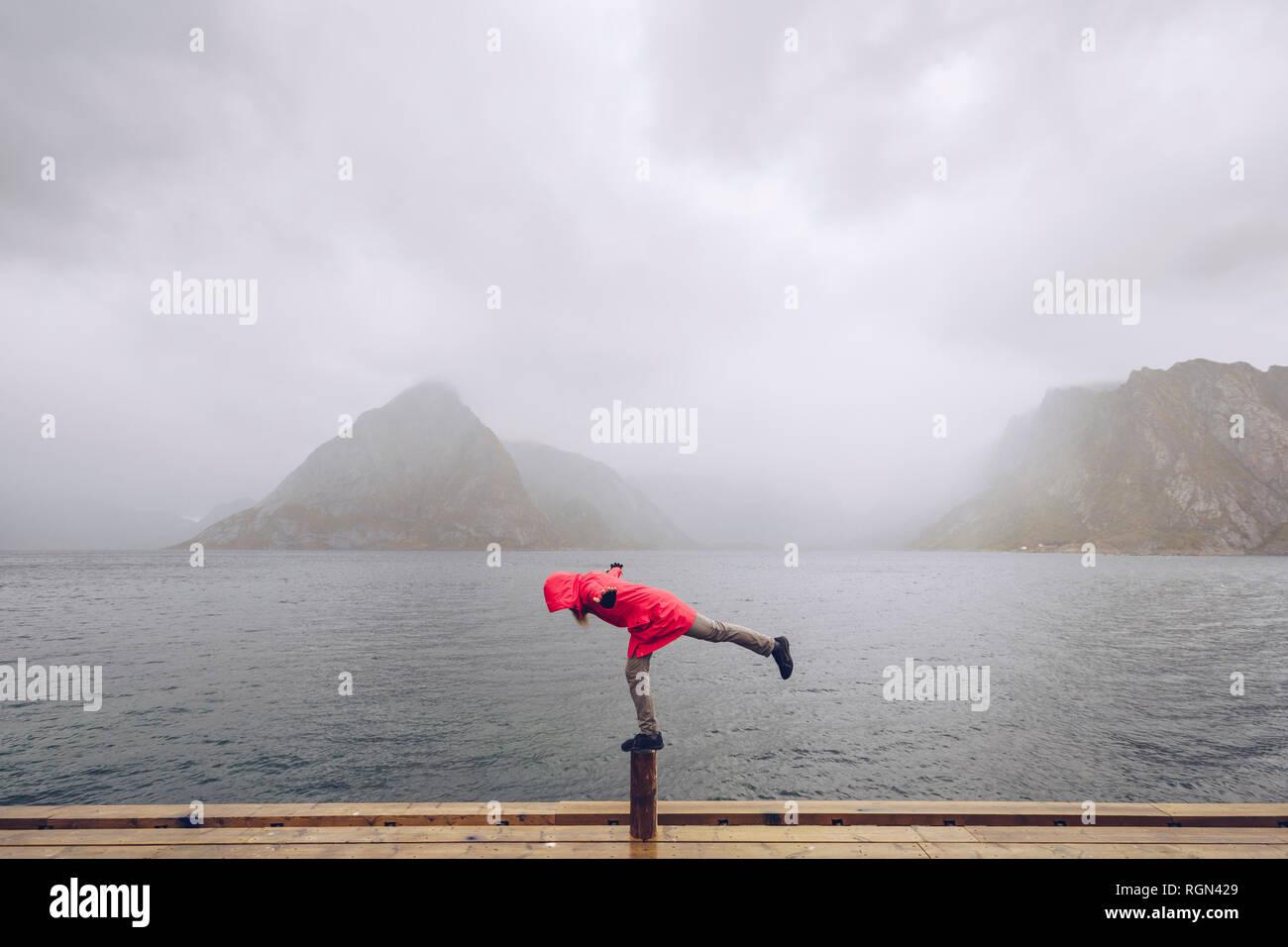 Norway, Lofoten, Hamnoy, man wearing red rain jacket balancing on wooden stake - Stock Image