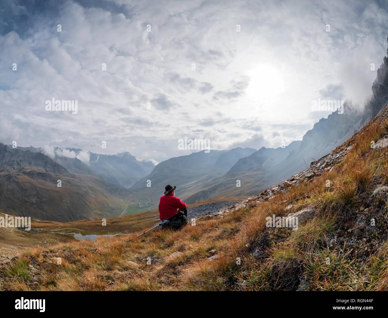 Border region Italy Switzerland, senior man having a break from hiking in mountain landscape at Piz Umbrail Stock Photo