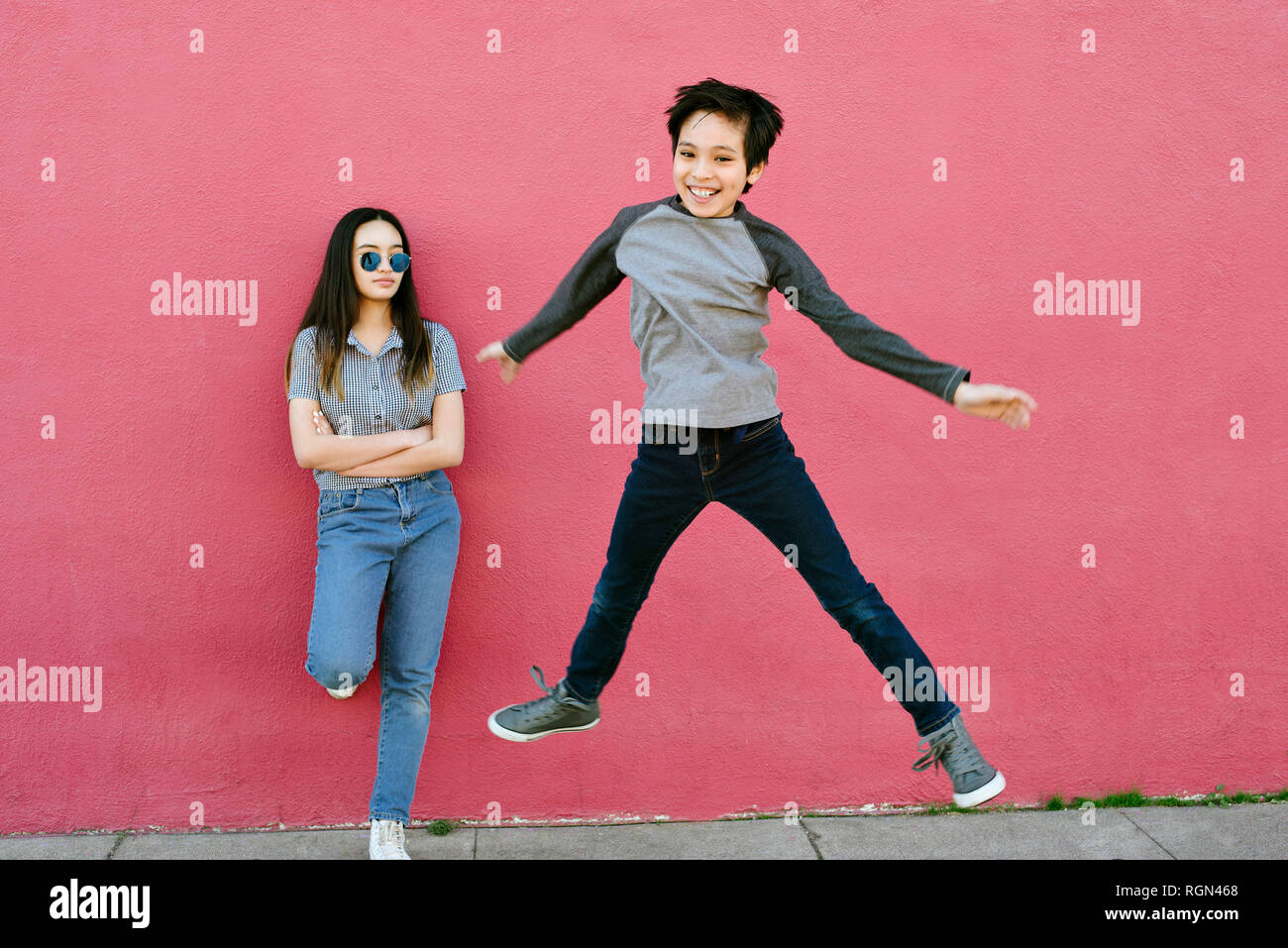 A teen sister looks onto her younger brother as he leaps into the air.  She is stoic and he is happy - Stock Image