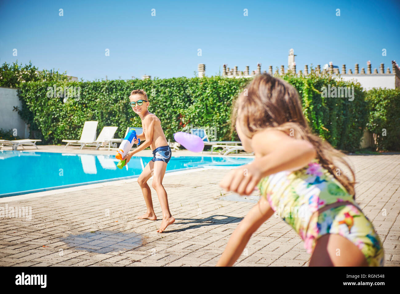 Girl and boy having a water fight with water gun and water bombs at the poolside - Stock Image