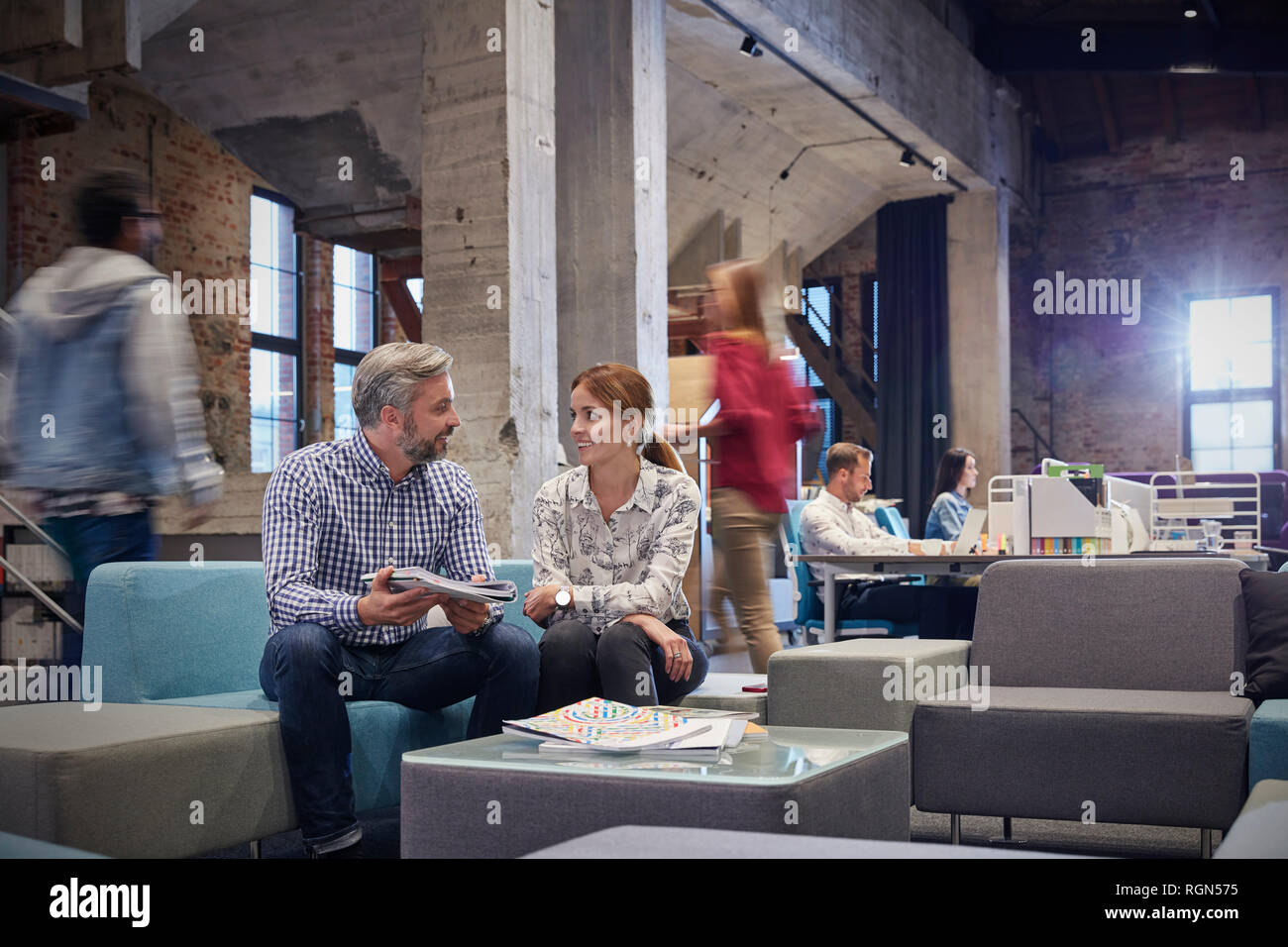 Business people having a informal meeting in communications pit - Stock Image