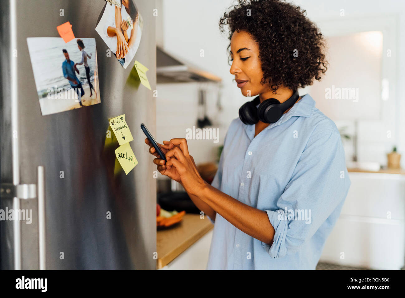 Woman in her kitchen in the morning, posting sticky  notes on the fridge - Stock Image