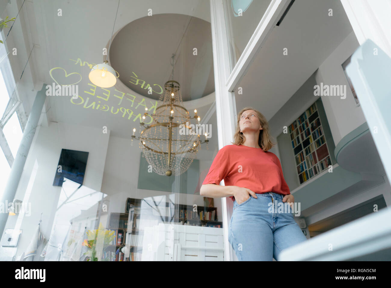 Low angle view of young woman standing in a cafe - Stock Image