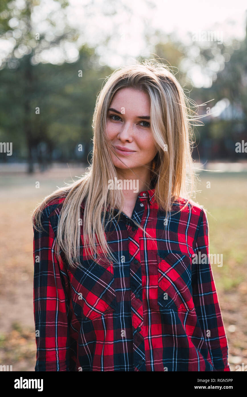 33a905da Portrait of blond young woman wearing plaid shirt in autumn - Stock Image