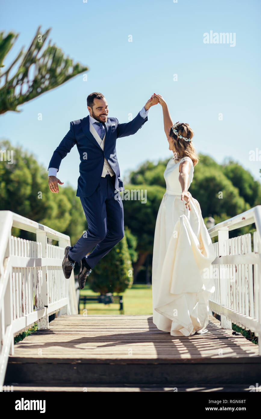 Bridal couple enjoying their wedding day in a park - Stock Image