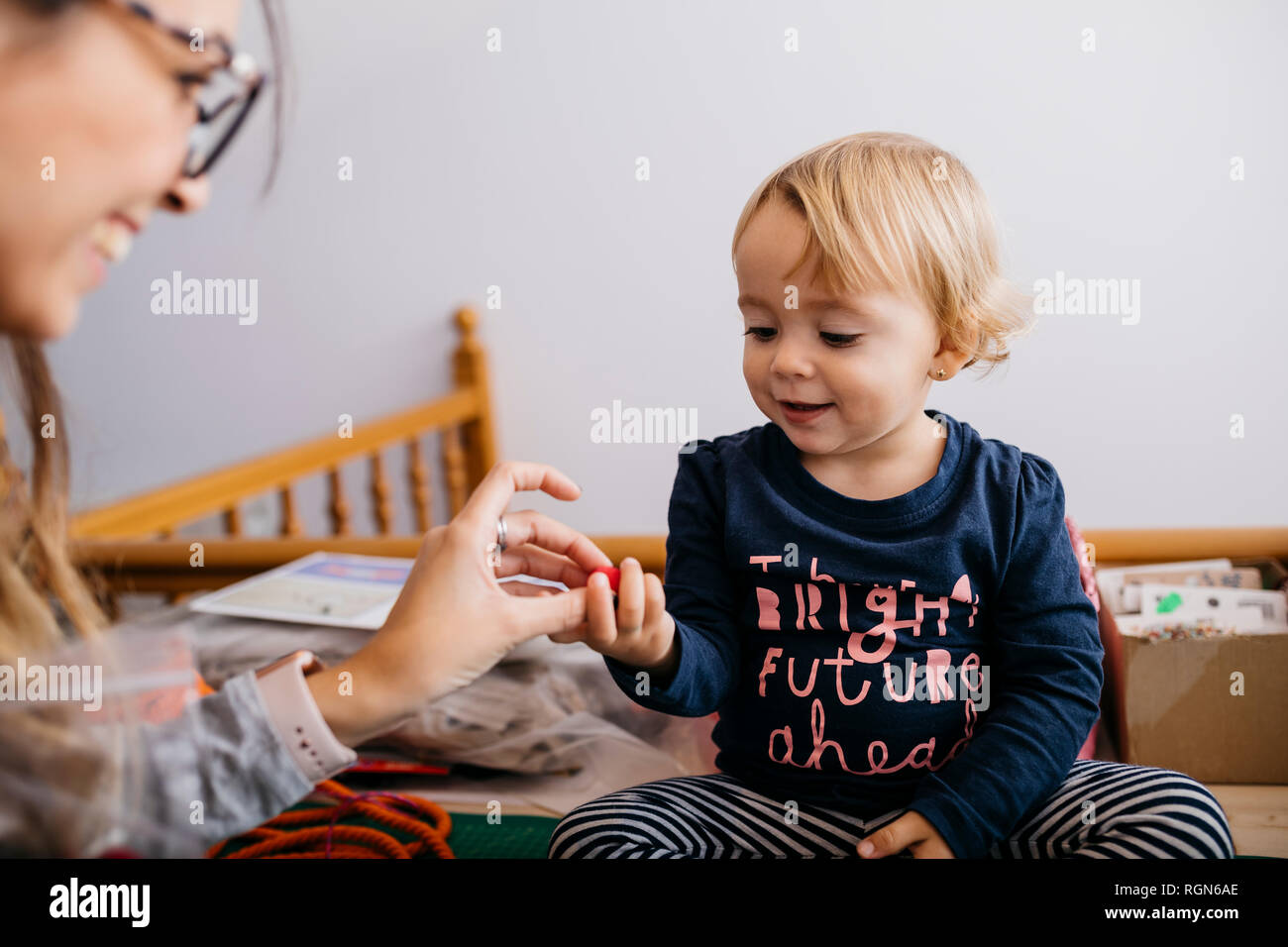 Mother giving fashion accessory to little daughter at home - Stock Image