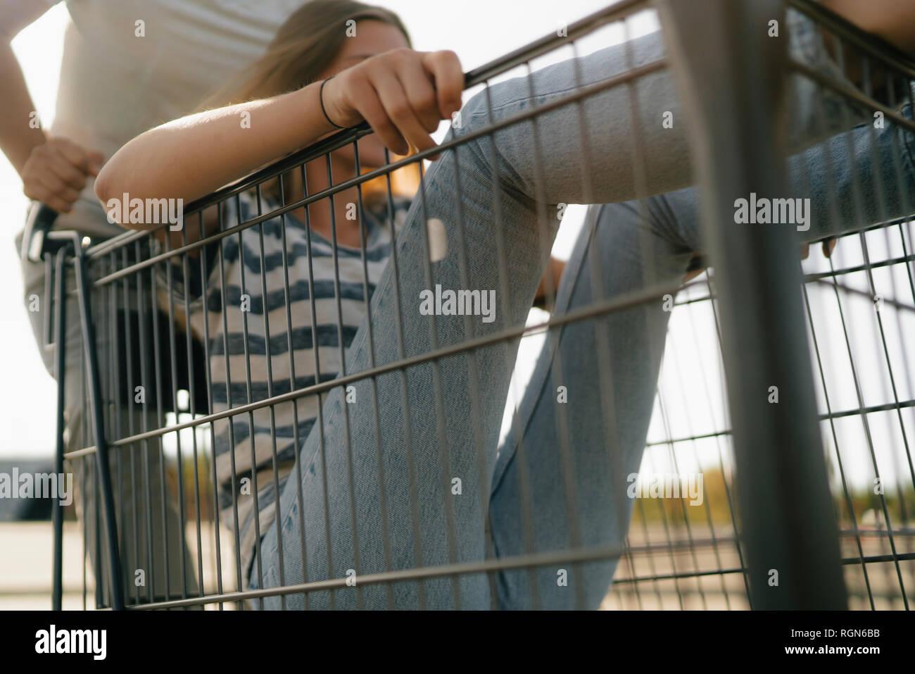 Carefree young man pushing girlfriend in a shopping cart Stock Photo