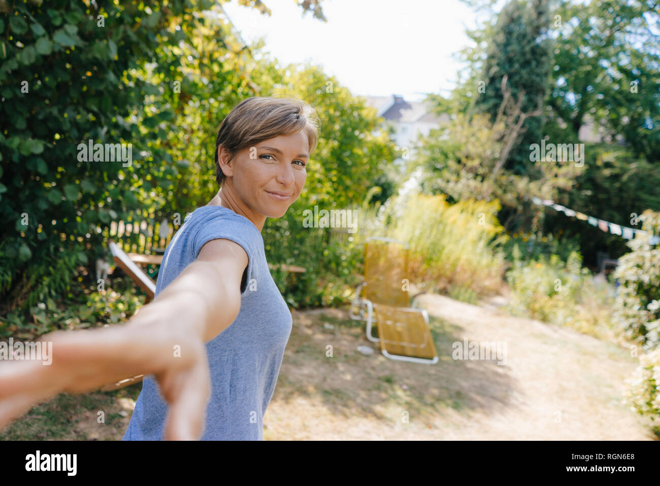 Portrait of smiling woman in garden reaching out Stock Photo