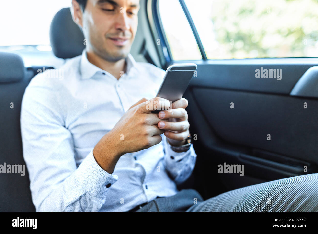 Man using cell phone on back seat of a car - Stock Image