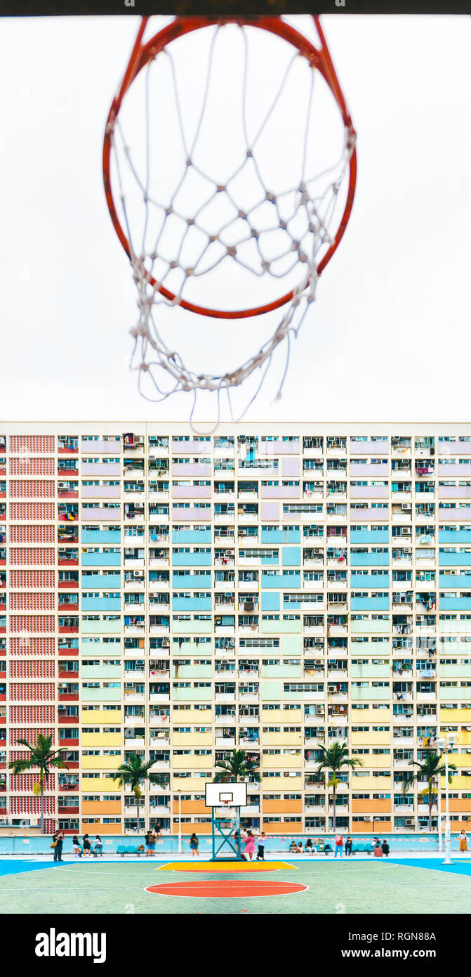 China, Hong Kong, Kowloon, basketball hoop, public housing in the background - Stock Image