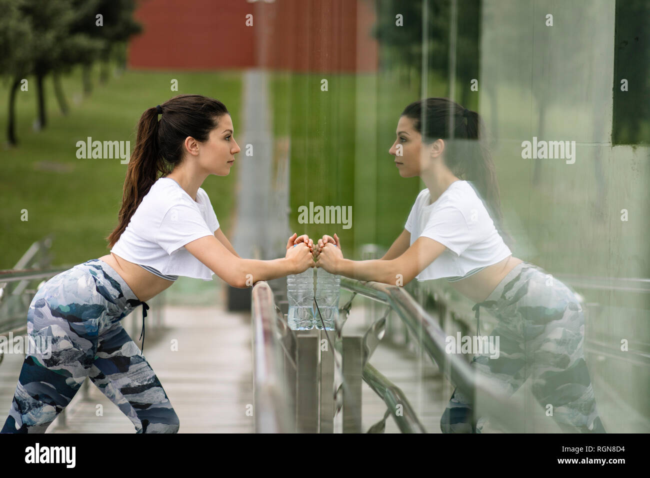 Young woman doing stretching exercise reflected in glass facade - Stock Image