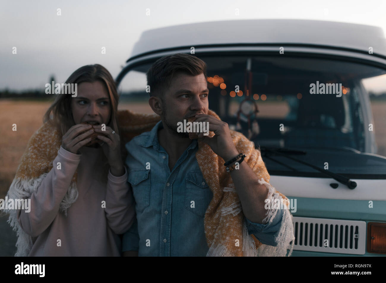 Couple wrapped in a blanket at camper van having a snack in rural landscape Stock Photo