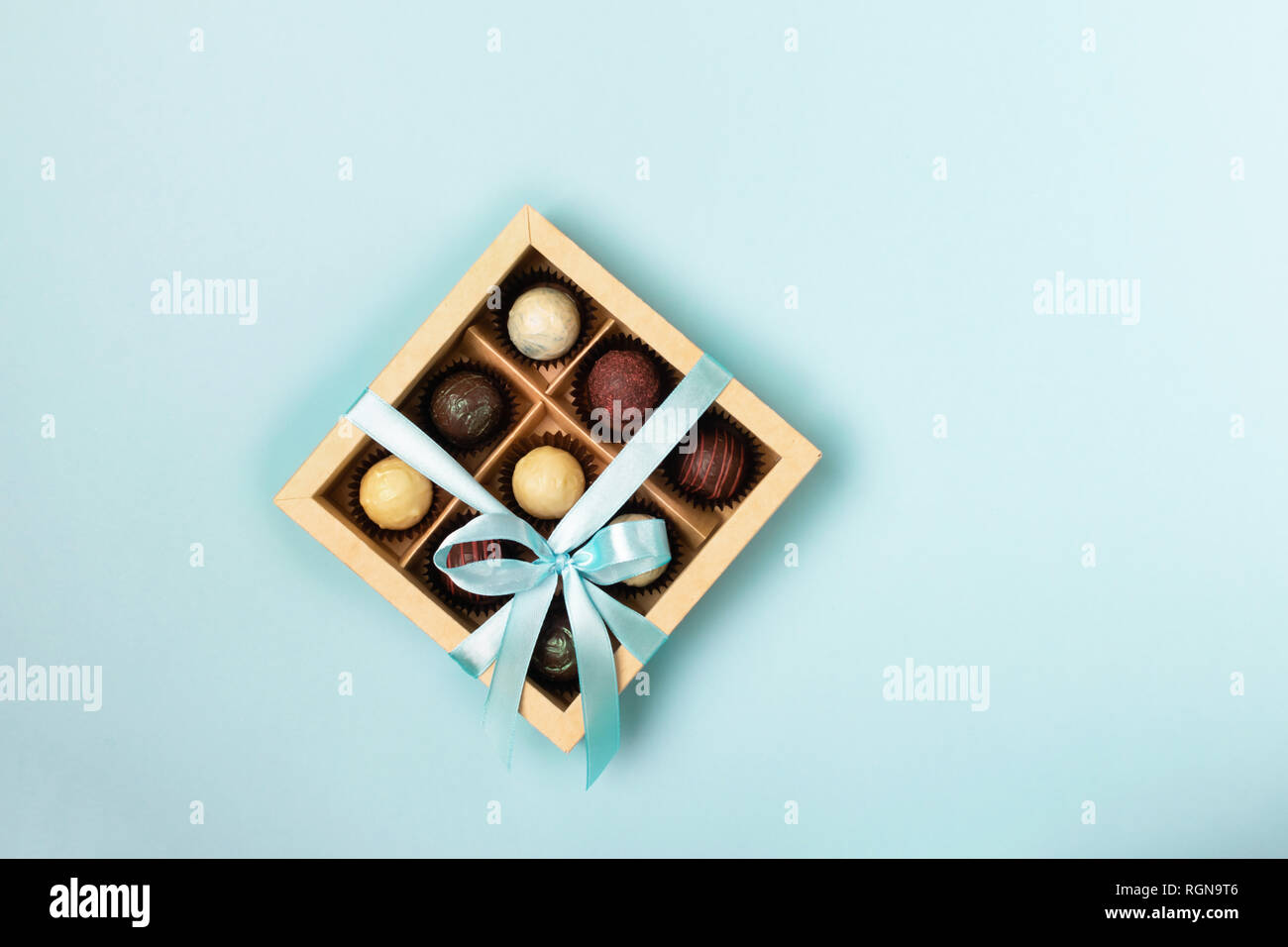 Various chocolates in crafting paper box with a satin blue ribbon on a bright blue background. Place for design. Flat lay. Festive concept. Copy space - Stock Image