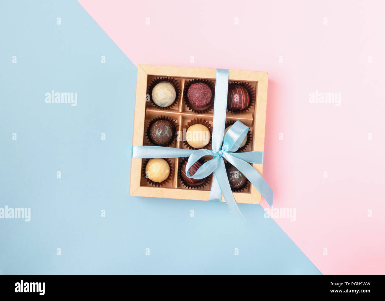 Various chocolates in crafting paper box with a satin blue ribbon on a brightly colored background. Place for design. Flat lay. Festive concept. Copy  - Stock Image