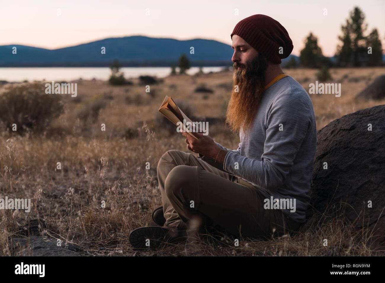 USA, North California, bearded young man reading a book near Lassen Volcanic National Park Stock Photo