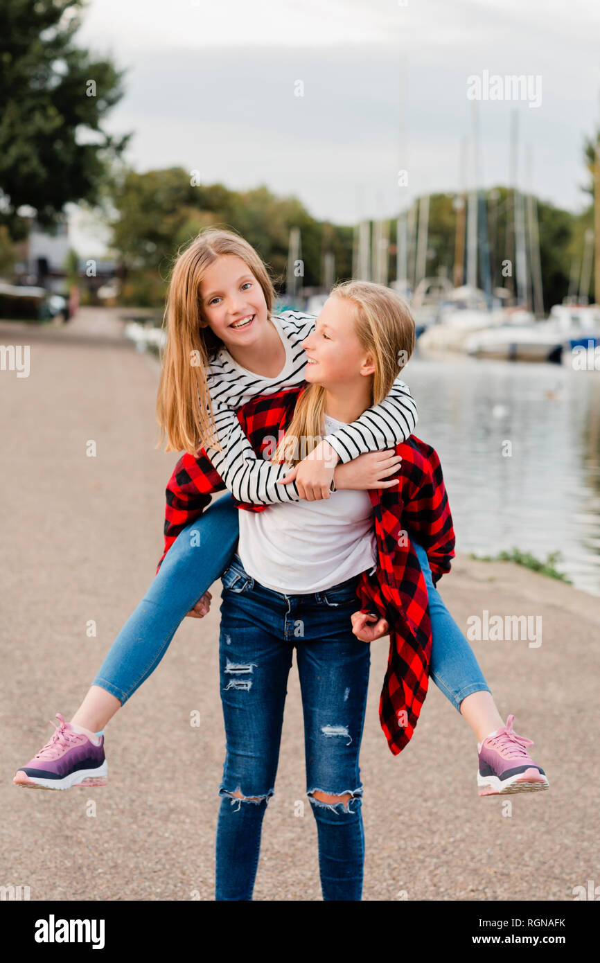 Girl giving her friend a piggyback ride - Stock Image