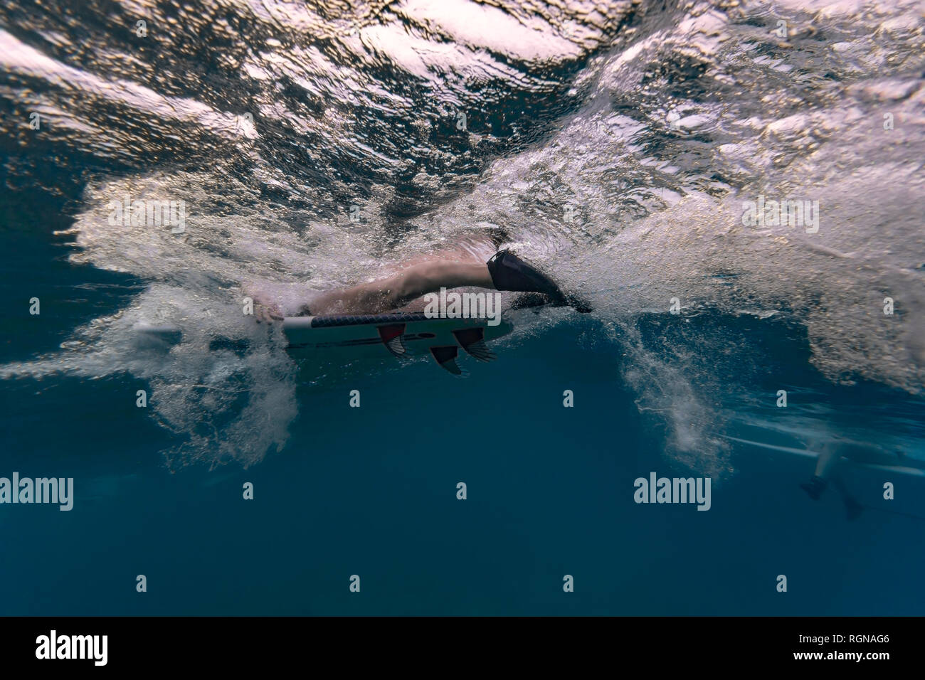 Maledives, Under water view of wave, surfer sitting on surfboard, underwater shot - Stock Image