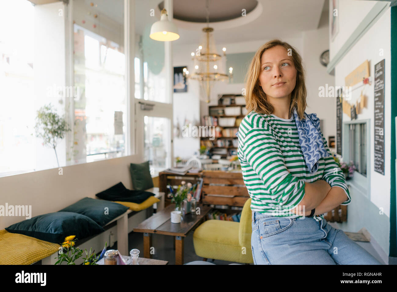 Young woman in a cafe looking sideways - Stock Image