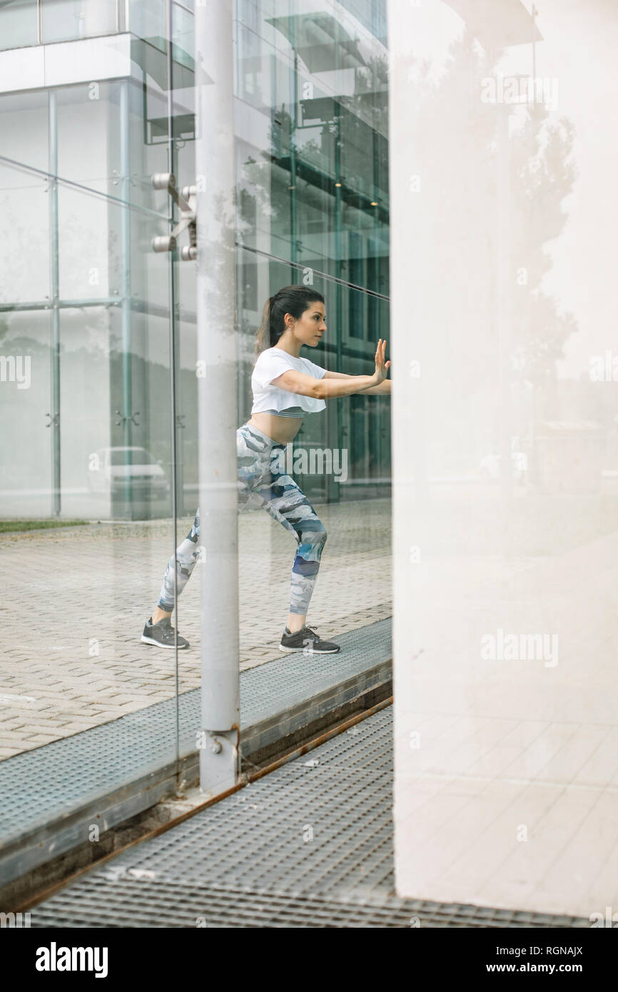 Young woman doing stretching exercise at glass facade - Stock Image