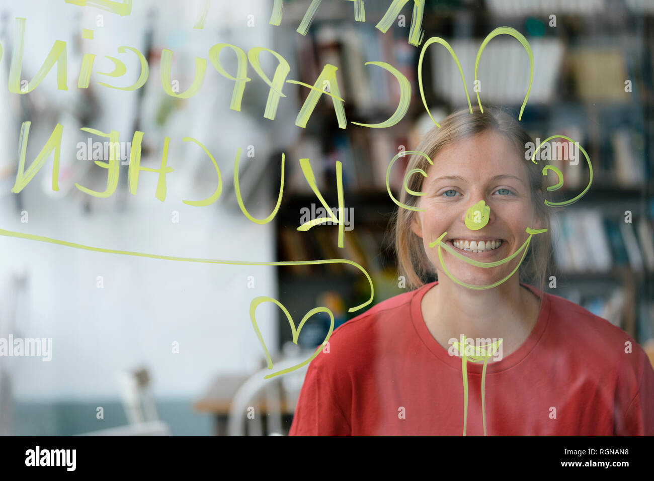 Portrait of happy young woman behind windowpane in a cafe - Stock Image