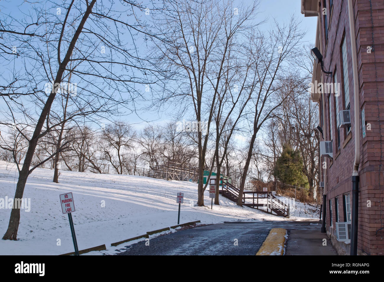A driveway next to a building in winter with snow and bare trees in Braddock Hills, Pennsylvania, USA - Stock Image