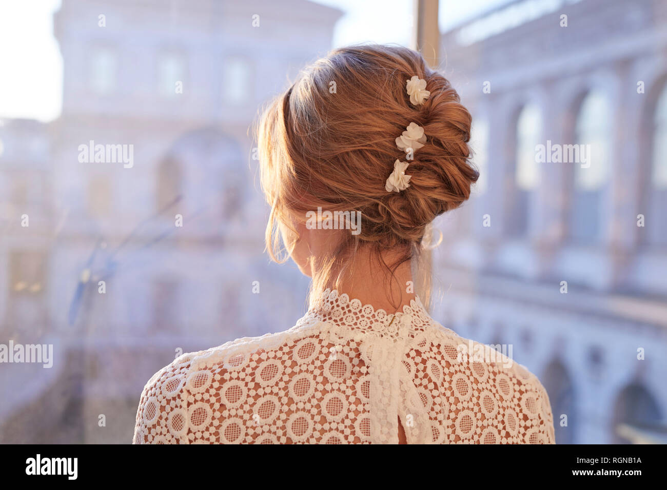 Portrait of blond bride, rear view, looking through window - Stock Image