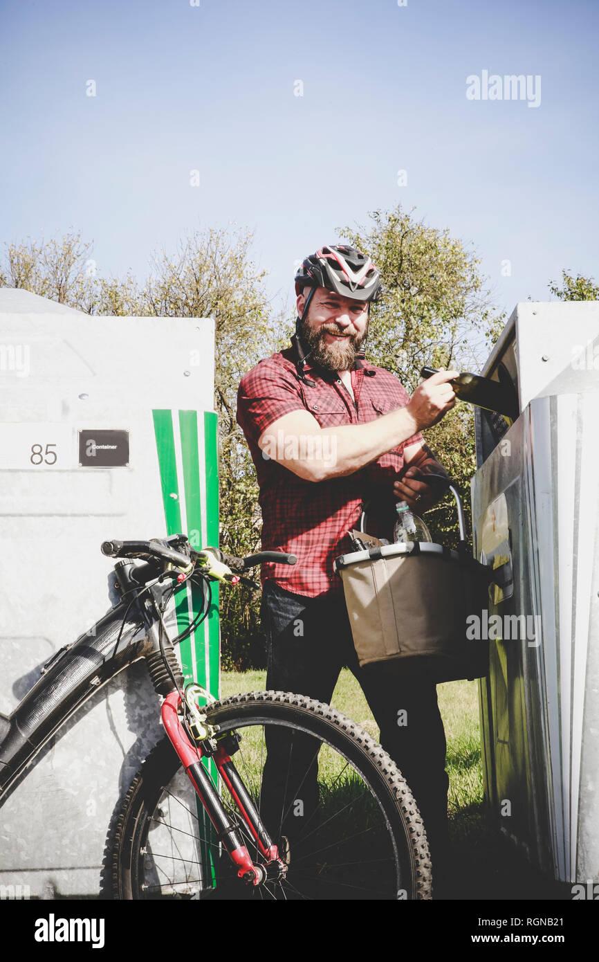 Portrait of man recycling glass bottle in bottle cyclist Stock Photo