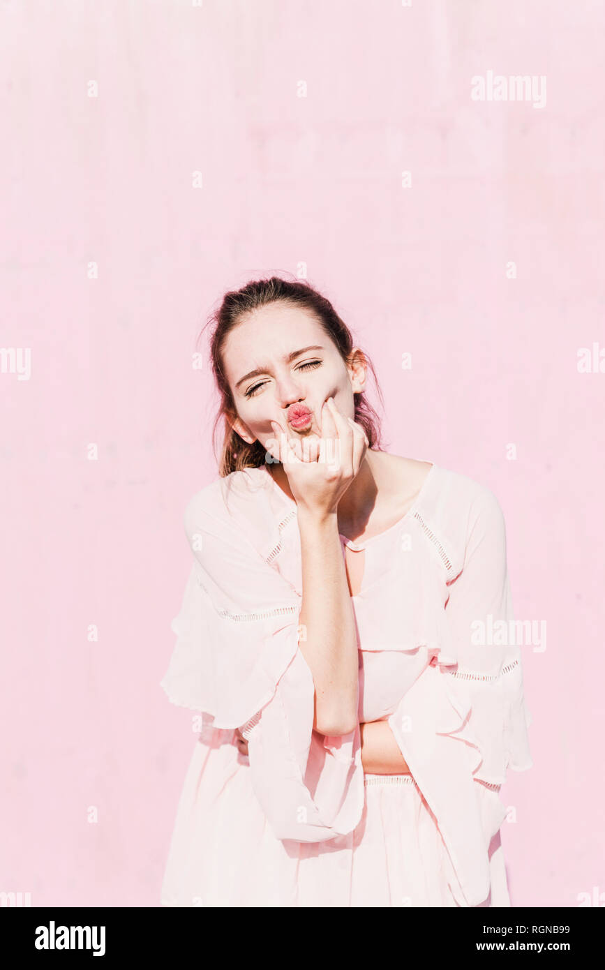 Portrait of young woman grimacing in front of pink wall - Stock Image