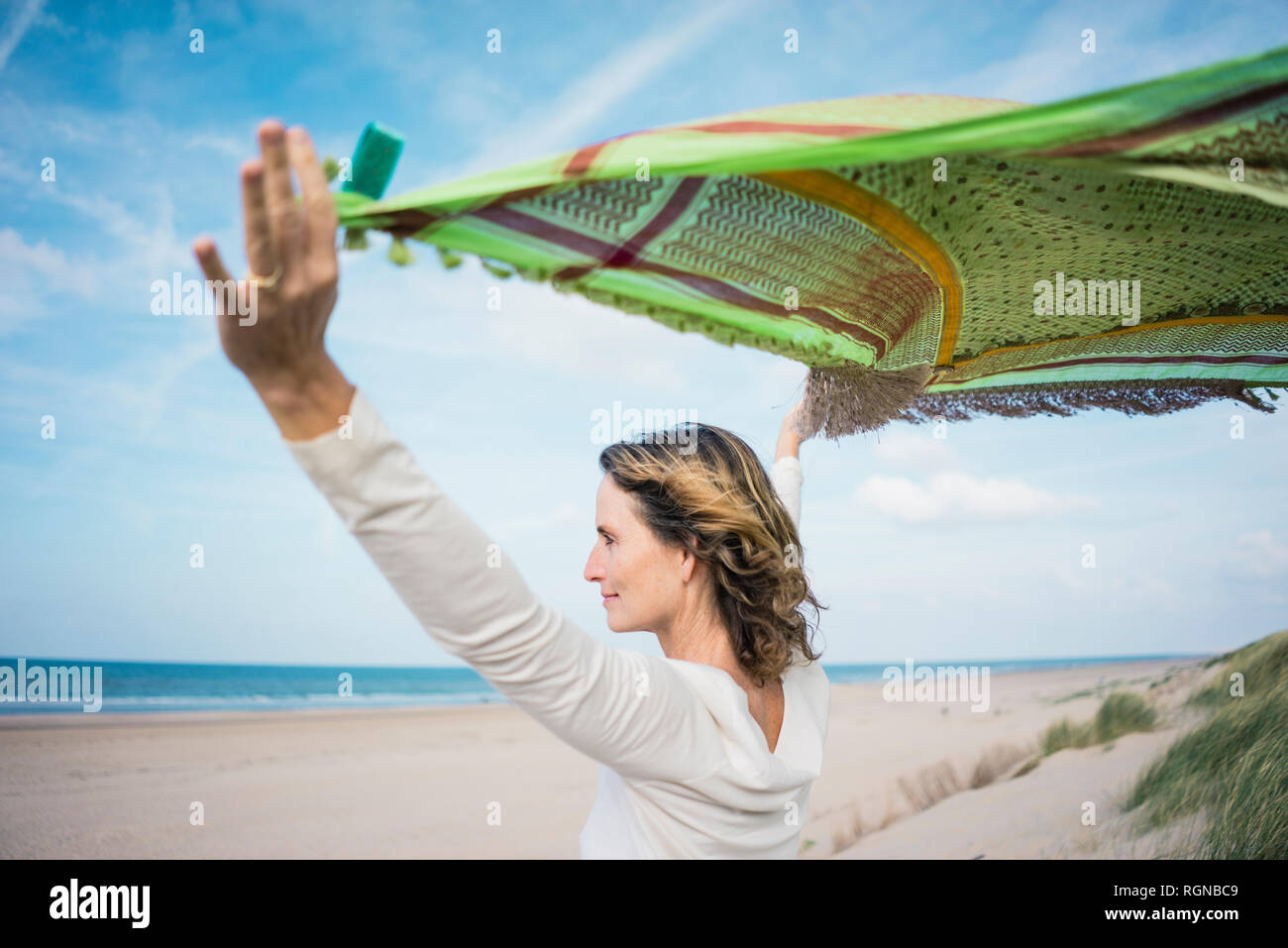 Mature woman holding flapping scarf in the wind, relxiang in the dunes - Stock Image