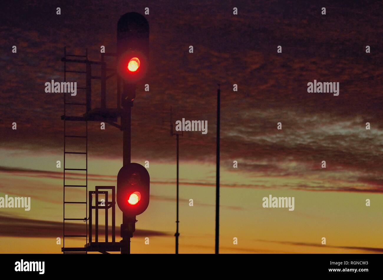 Orland Park, Illinois, USA.  A red signal protecting a block of railroad tracks just after sunset. - Stock Image