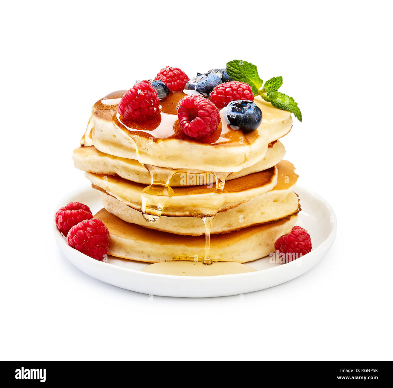 Delicious pancakes with berries, honey or maple syrup. Homemade pancakes and sweet syrup on white plate isolated. - Stock Image