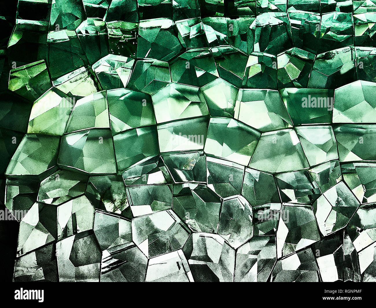 Close-up of a mosaic of retro style green colored, 3 dimensional looking glass cubicals glued to each other with light shining through - Stock Image