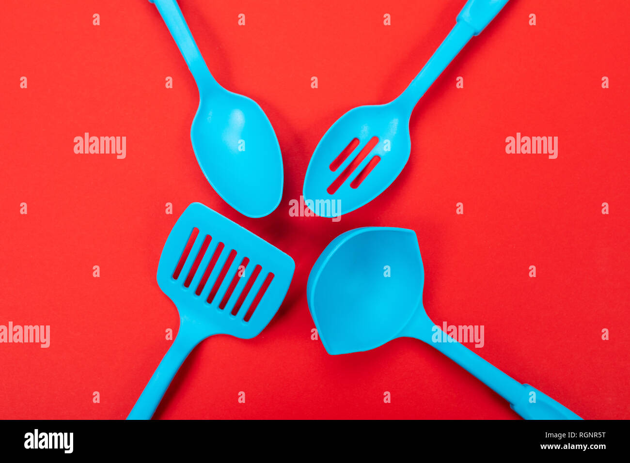 top view of blue kitchen utensils isolated on red background ...