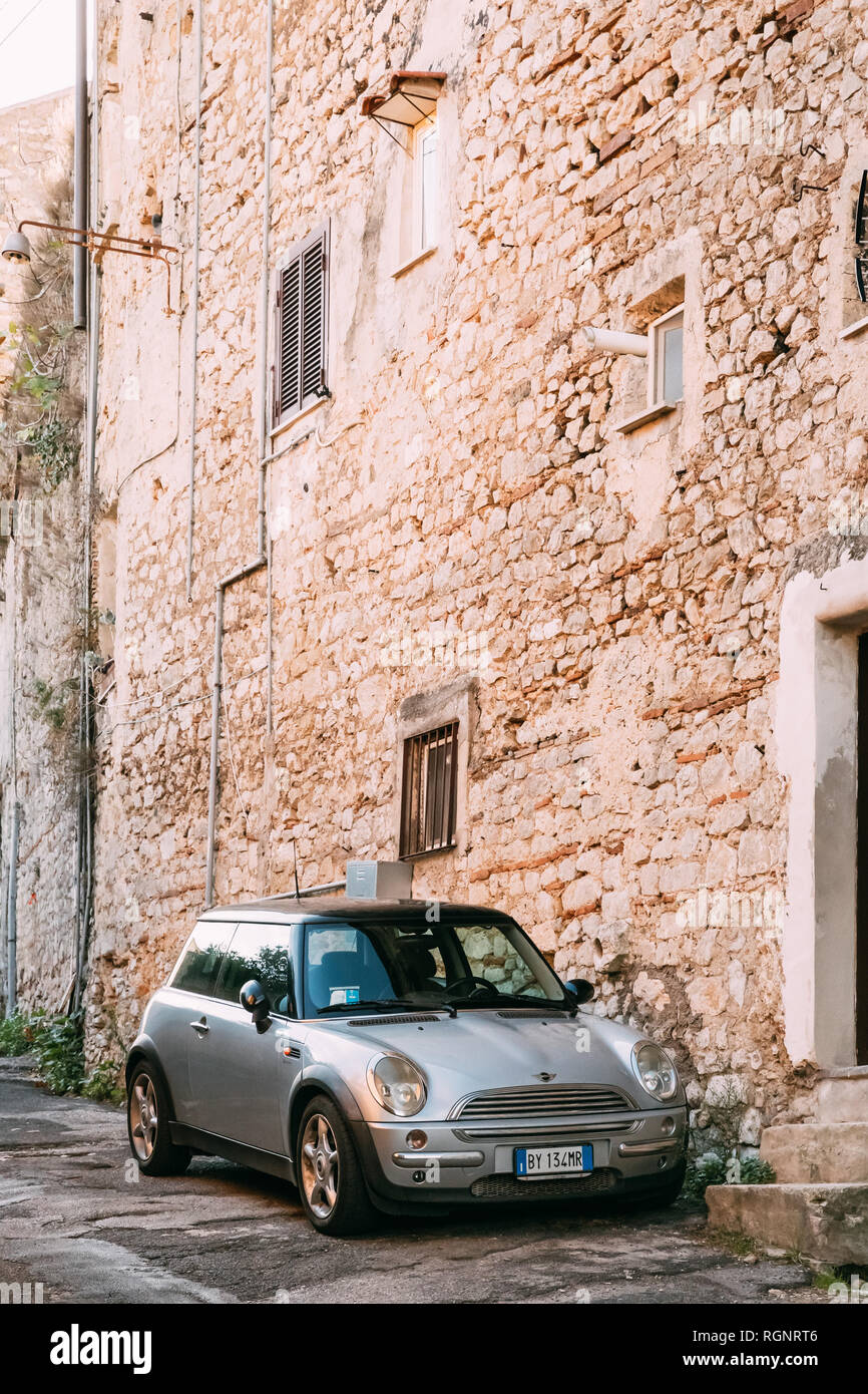 Terracina, Italy - October 15, 2018: Front View Of Gray Color 2004 Mini One Hatch (pre-facelift model) Mini Cooper Car Parking On Street Near Old Ital Stock Photo