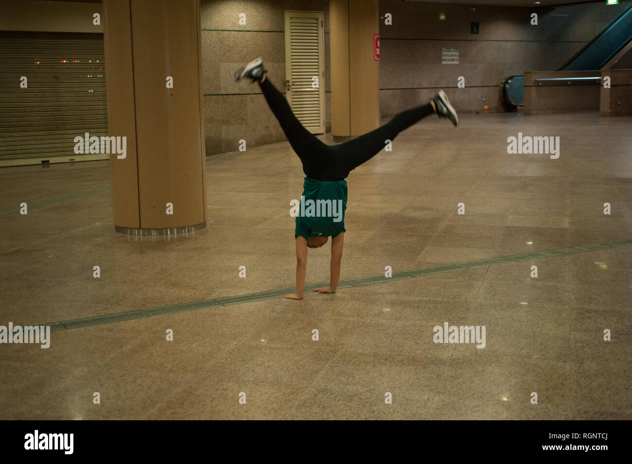 10.02.2018, Singapore, Republic of Singapore, Asia - A young woman is doing a cartwheel in an air-conditioned underpass in Singapore's city centre. - Stock Image