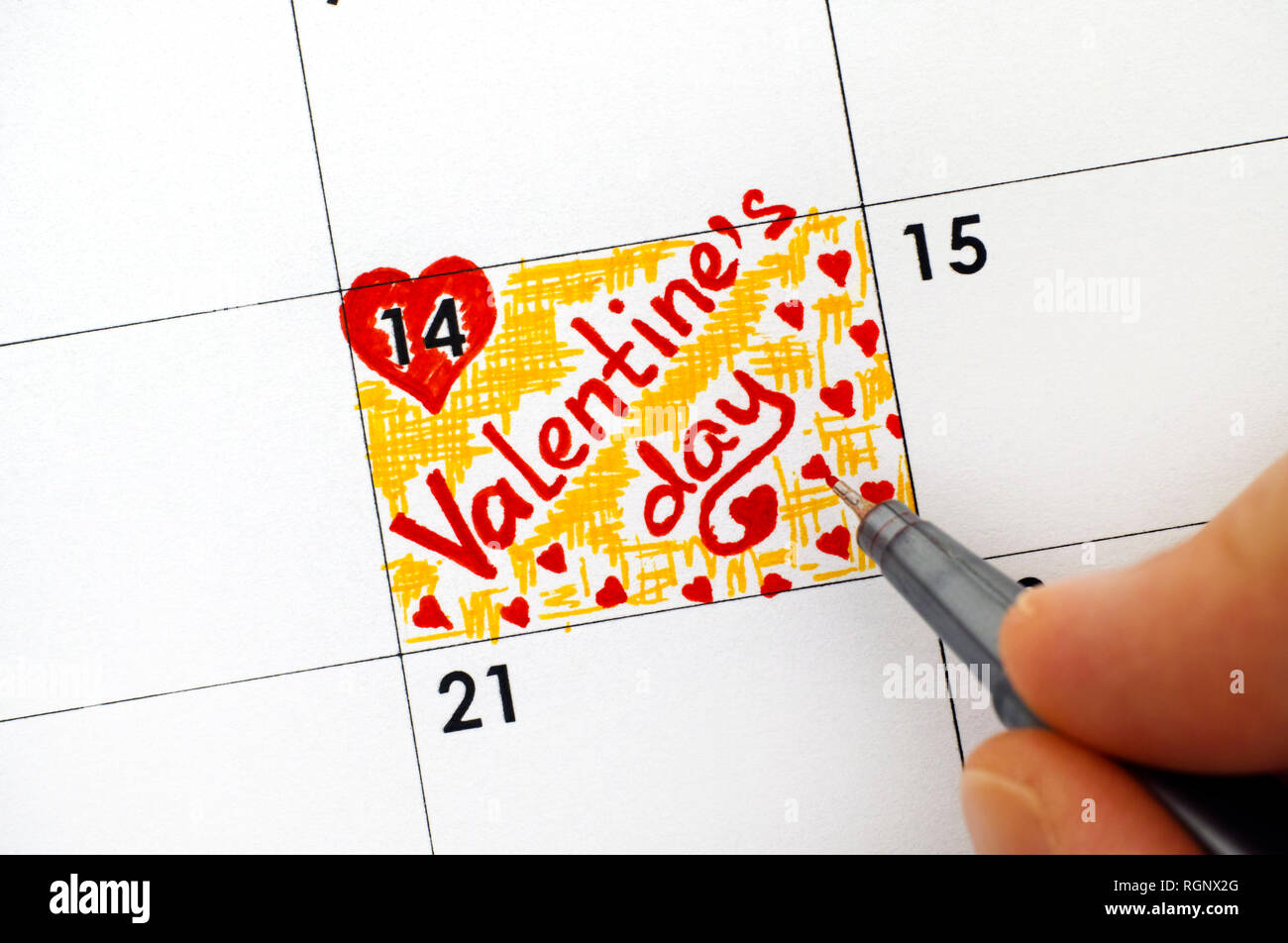 Woman fingers with pen writing reminder Valentines Day in calendar. Close-up. - Stock Image