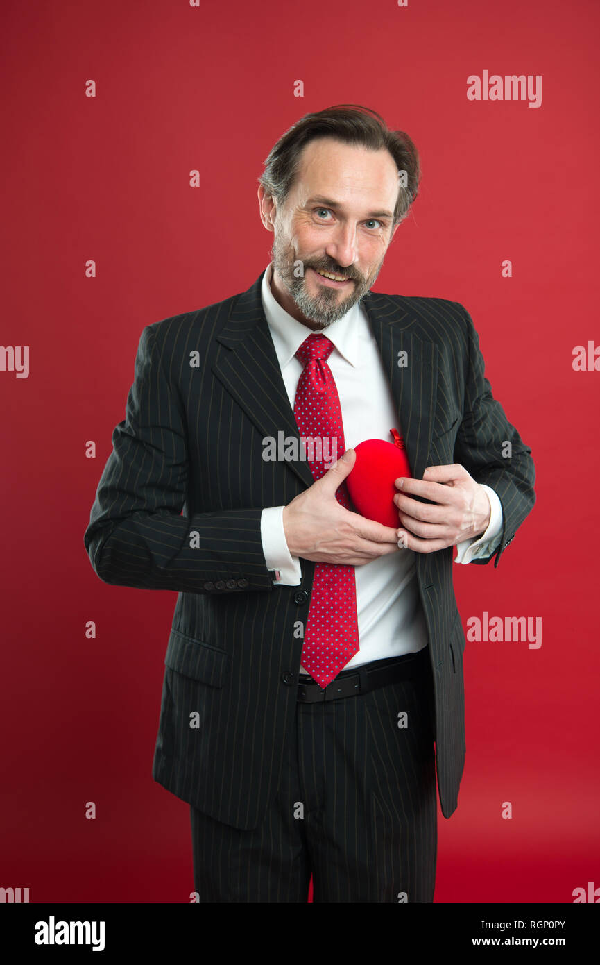 Pure feelings. Man mature handsome guy wear elegant suit hold red heart. Valentines day celebration. Romantic surprise. Celebrate valentines day. Prepare gift for valentine. Love date anniversary. - Stock Image