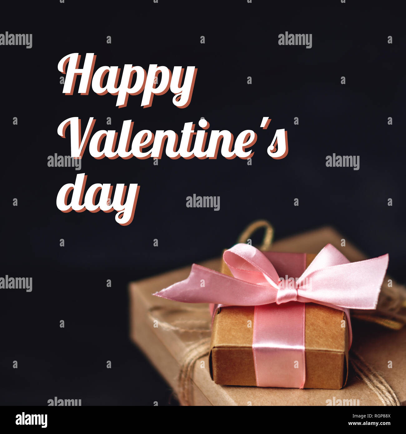 Holiday gift boxes Packed in crafting paper on dark wooden background. Square card Happy Valentine's day with text - Stock Image