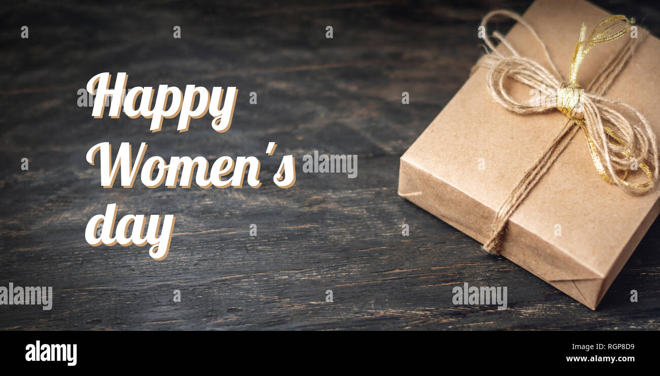 Holiday gift box Packed in crafting paper on dark wooden background. Holiday horizontal card Happy Women's day with text - Stock Image