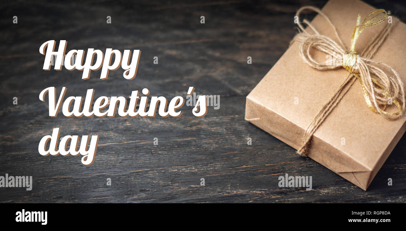 Holiday gift box Packed in crafting paper on dark wooden background. Holiday horizontal card Happy Valentine's day with text - Stock Image