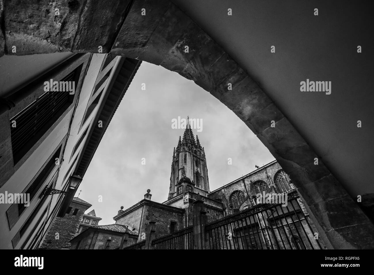 Black and white from below wonderful high tower of construction near stone buildings - Stock Image