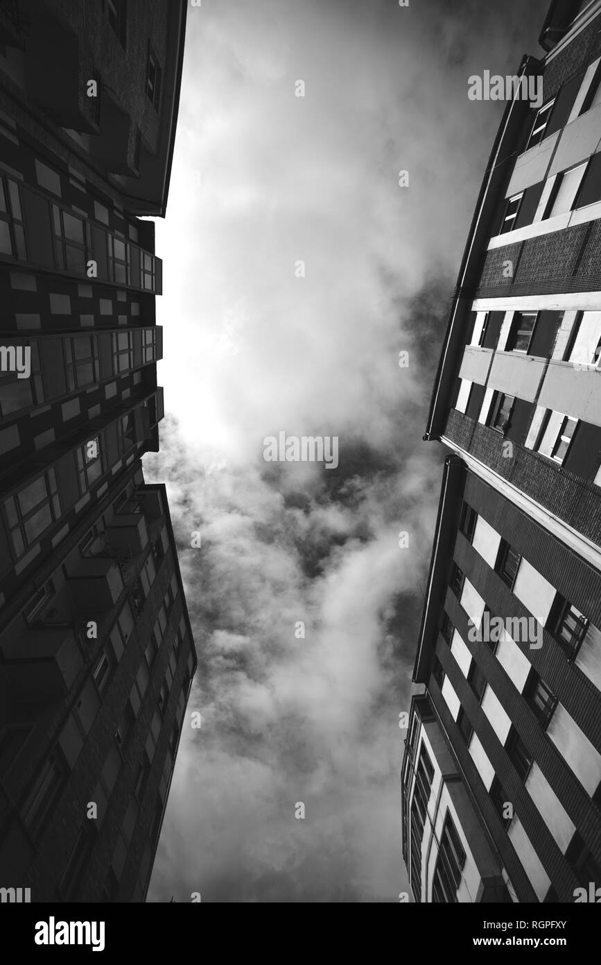 Black and white from below facades of block of flats with many windows and cloudy heaven - Stock Image