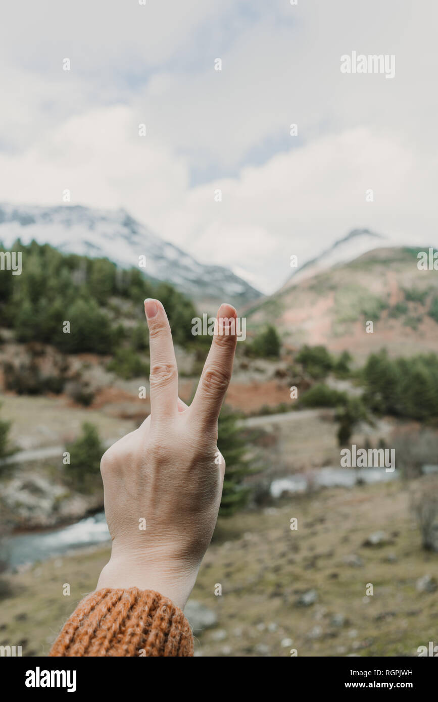 Crop hands of lady showing victory gesture and picturesque view of valley with wonderful mountains and cloudy heaven in Pyrenees - Stock Image